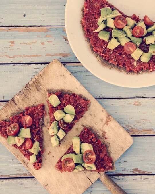 Pizza cruda con pomodorini e avocado.